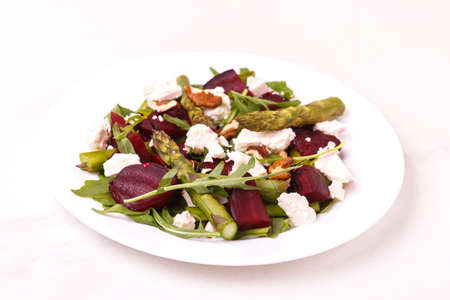 Green vegan salad with asparagus, feta, beetroot, arugula, lime and nuts. The concept of dietary vegetarian food. Top view