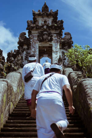 Hindu monks are climbing the stairs to the temple Lempuyang, Bali, Indonesia Stock Photo