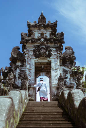 Hindu monk stands in the gate of temple Lempuyang, Bali, Indonesia Stock Photo