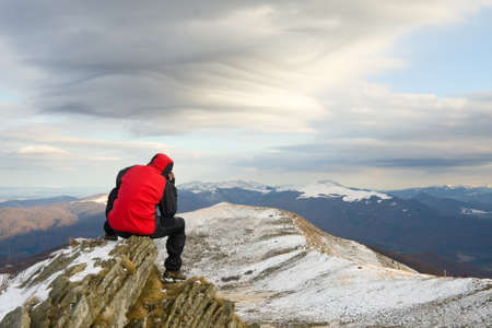 Lonely mountain climber on top of a mountain  photo