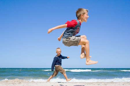 ビーチでジャンプ笑顔の 2 人の男の子 写真素材