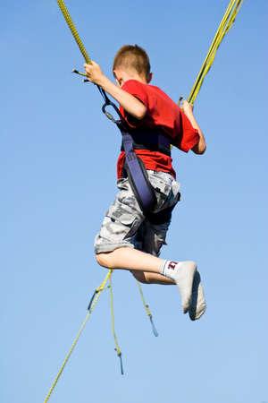 bungee jumping: El ni�o peque�o que salta en el trampol�n (bungee jumping).