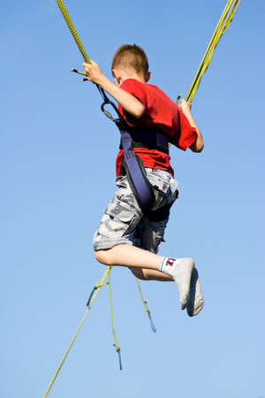 트램 폴린 (번지 점프)에 점프 어린 소년.