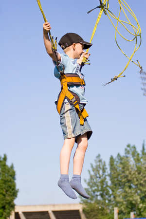 Little boy jumping on the trampoline (bungee jumping).  photo