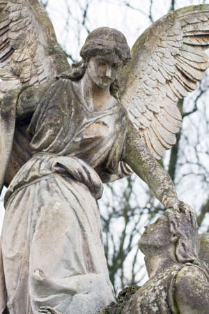 angel headstone: statue in a cemetery at fall