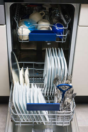 Dishwasher with white plates and steel cutlery  Stock Photo - 17536568