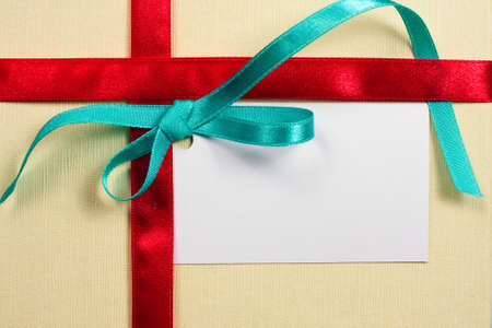 Blank gift tag tied with a bow of red satin ribbon   photo