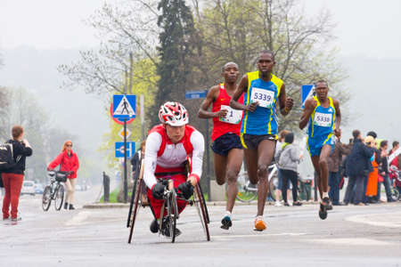 cracovia:  KRAKOW, POLAND - APRIL 28   Cracovia Marathon Handicapped man marathon runners in a wheelchair and other runners on the city streets on April 28, 2013 in Krakow, POLAND