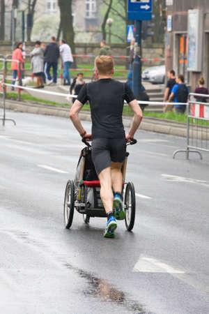 cracovia: KRAKOW, POLAND - APRIL 28 : Cracovia Marathon. Wladyslaw Wachulec with his son in a wheelchair on the city streets on April 28, 2013 in Krakow, POLAND  Editorial