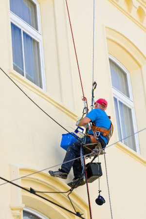 steeplejack: Prague - August 20, 2011. Painter are painting facade of building with roller on August 20, 2011 in Prague Editorial