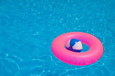 カラフルなボールを膨らませるとプールに浮かんでいるラウンド チューブ 写真素材