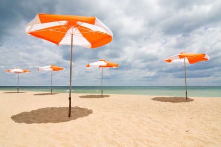Beach umbrellas on sand beach. Concept for rest, relaxation, holidays, spa, resort.  photo
