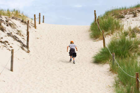 lonely boy walking through a sand dune  photo