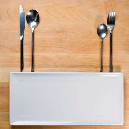 Empty plate with fork and knife on wooden table, table arrangement photo