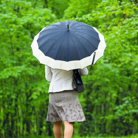 walking in the rain: Woman under Rain with umbrella Stock Photo