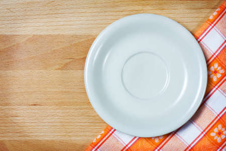Empty plate on tablecloth over wooden background  photo