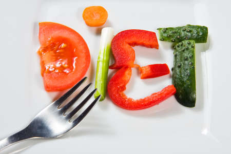 Plate with vegetables and word diet over wooden background  photo