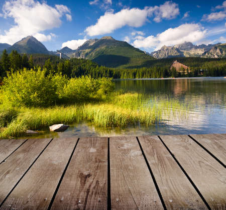 mountain lake and empty wooden deck table photo