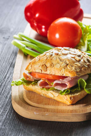 Fresh ham sandwich on wooden board - close up  photo