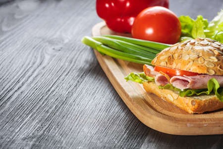 A fresh deli sandwich with ham, radish, tomatoes photo