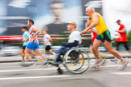 KRAKOW, POLAND - MAY 28 : Cracovia Marathon. Unidentified handicapped man in  marathon on a wheelchair on the city streets on May 18, 2014 in Krakow, POLAND