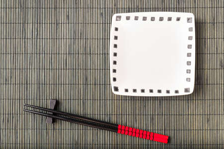 Two chopsticks on sushi mat background with plate photo