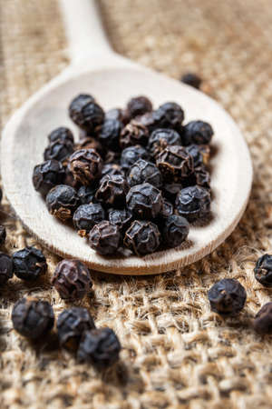 black pepper on the wooden spoon photo