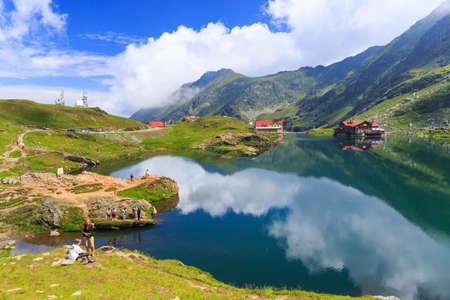 BALEA LAKE, ROMANIA - JULY 21: Unidentified tourists enjoy the sights of Balea Lake at 2,034 m altitude on July 21, 2014 in  Fagaras Mountains, Romania.