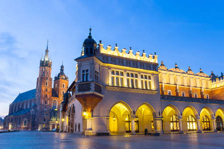Sukiennice and St. Marys Church at night in Krakow, Poland. photo