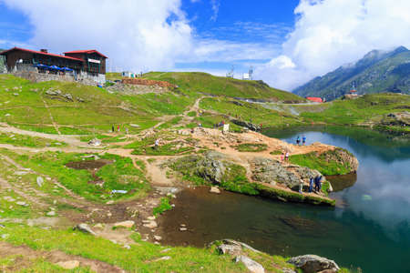 balea: BALEA LAKE, ROMANIA - JULY 21: Unidentified tourists enjoy the sights of Balea Lake at 2,034 m altitude on July 21, 2014 in  Fagaras Mountains, Romania.