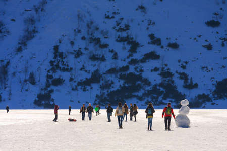 morskie: Morskie Oko Lake, POLAND - MARCH 14: Unidentified group of tourists are walking on the frozen Morskie Oko Lake, Poland on March 14, 2014.Tatra Mountains is very popular travel destination.