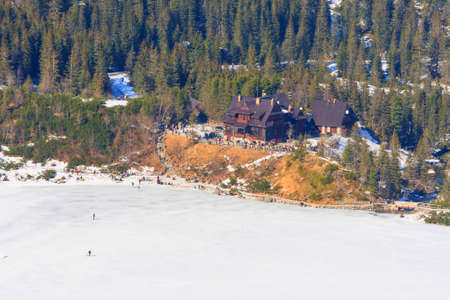 oko: Morskie Oko Lake, POLAND - MARCH 14: Unidentified group of tourists are walking on the frozen Morskie Oko Lake, Poland on March 14, 2014.Tatra Mountains is very popular travel destination.