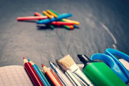School supplies on black background, vintage color tone photo