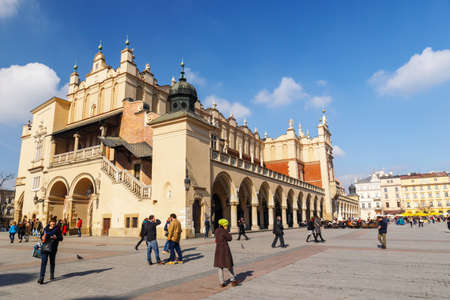 KRAKOW, POLAND - March 07 2015: Tourists enjoying an spring day in The Grand Central Square in front of the The Renaissance Sukiennice also known as The Cloth Hall, Krakow, Poland March 07 2015