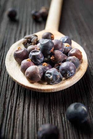 juniper: juniper berries on old wooden spoon Stock Photo