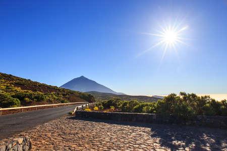 sunlight: Sun with sunlight over mountains on blue sky with fog and Teide volcano, Tenerife, Canary Islands, Spain Stock Photo