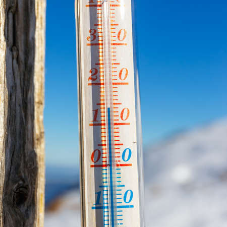 strapped: thermometer strapped on a post outside in the mountain, shallow depth of field Stock Photo