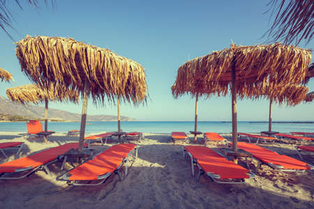sun umbrellas: Sun umbrellas and chairs on beach, vintage look