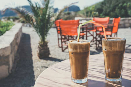 greek cuisine: Coffee frappe, greek cuisine on the table at the beach, vintage look