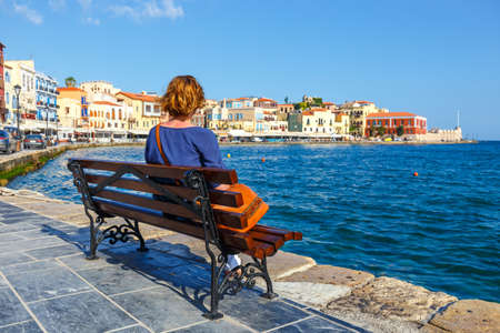 young woman sitting on the  bench and looking at old port in Chania, Crete, Greece Zdjęcie Seryjne
