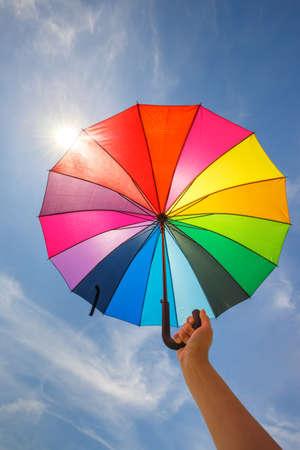 rainbow umbrella: open colorful rainbow umbrella on blue sky background Stock Photo