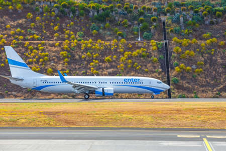 Funchal, Madeira - July 6, 2016: Enter Air Boeing 737 lands at Funchal Cristiano Ronaldo Airport. This airport is one of the most dangerous airports in Europe