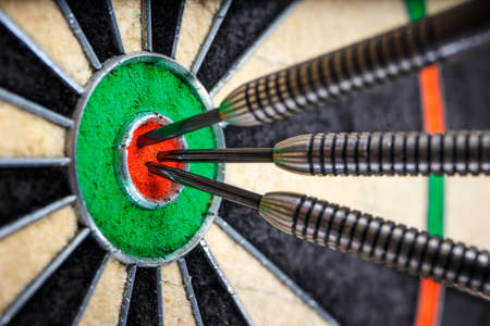 three darts in bulls eye, close up
