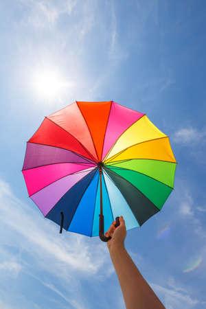 rainbow umbrella: open colorful rainbow umbrella on blue sky background, vintage look