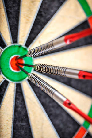 bull's eye: three darts in bulls eye, close up