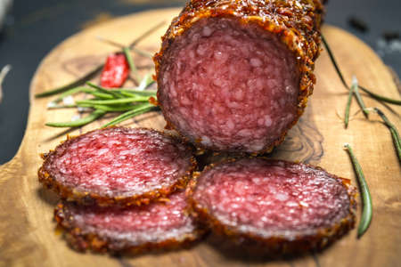 pepper salami: dried salami crusted in ground red pepper on dark background