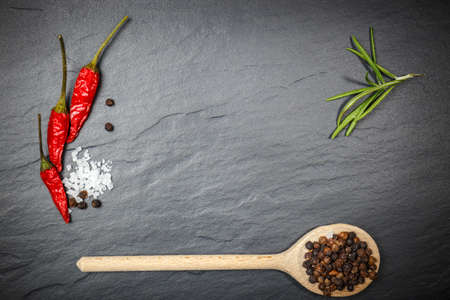 photography background: Chili with black pepper and salt on rustic stone background. Overhead view food photography.