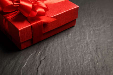 ruban noir: Red gift box with ribbon on dark stone background with copy space Banque d'images