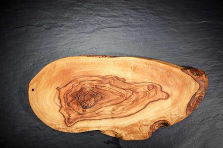 黒い石の背景にオリーブ木まな板