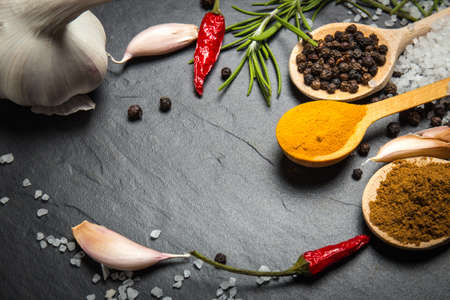 red stone: spices and herbs over black stone background, top view with copy space Stock Photo